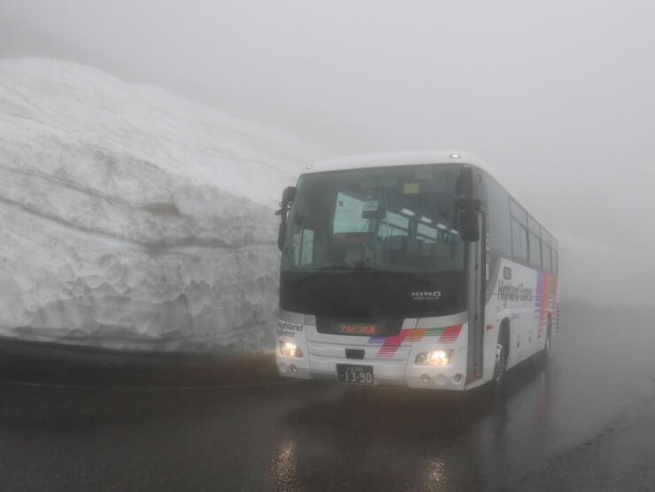 乗鞍高原で雪壁の間を試運転するバス