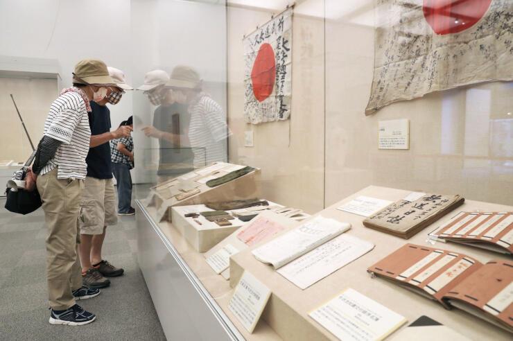 寄せ書きの日章旗や戦地からの手紙などが展示された企画展「戦後75年 私の戦争体験記」=長岡市の県立歴史博物館