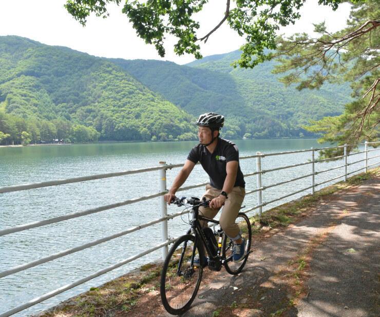 電動アシスト自転車で木崎湖畔を案内する西沢社長。7月からガイドツアーを始める=29日、大町市平