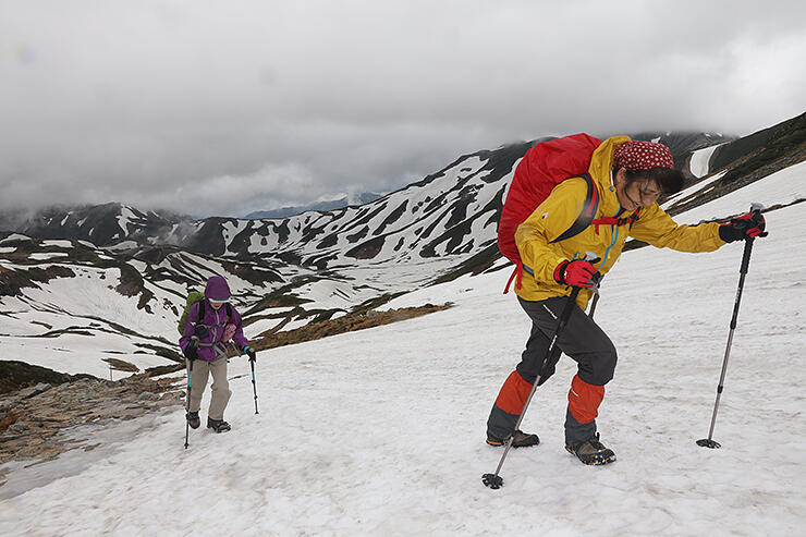 残雪の山々を背に、雄山を目指す登山者=立山・一ノ越付近