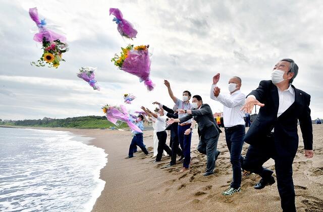 シーズン中の安全を願い、海に花束を投げ入れる関係者=7月1日、福井県坂井市三国町の浜地海水浴場