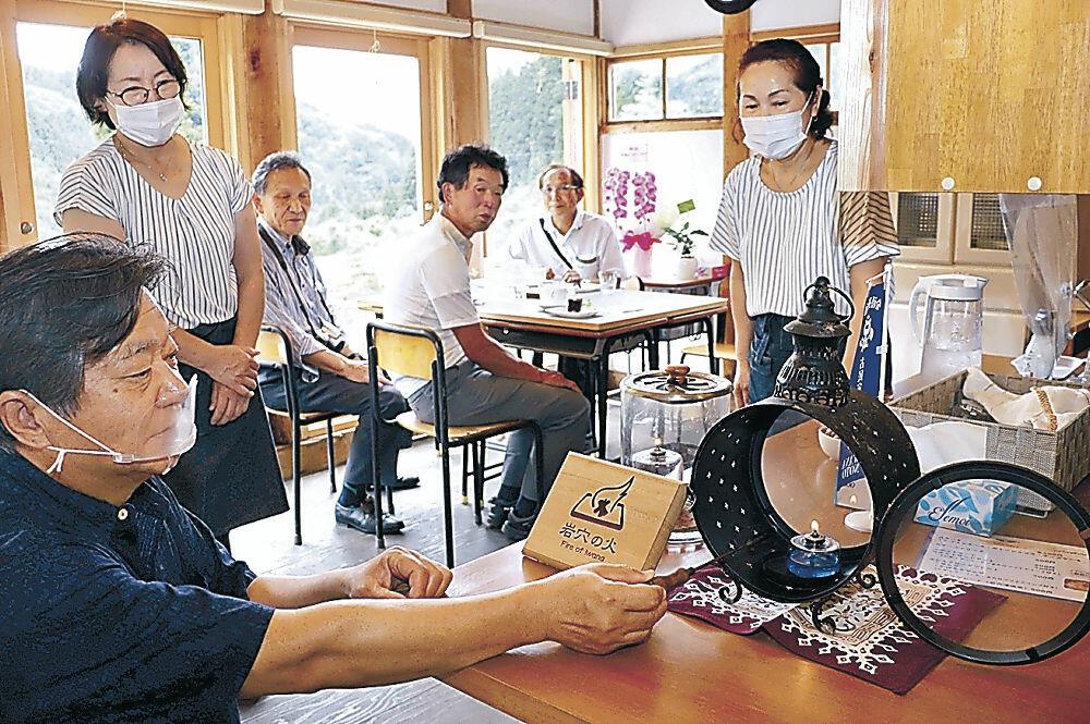 火様の種火でランプをともす森田さん(左)=七尾市中島町河内のカフェ「分福茶釜」