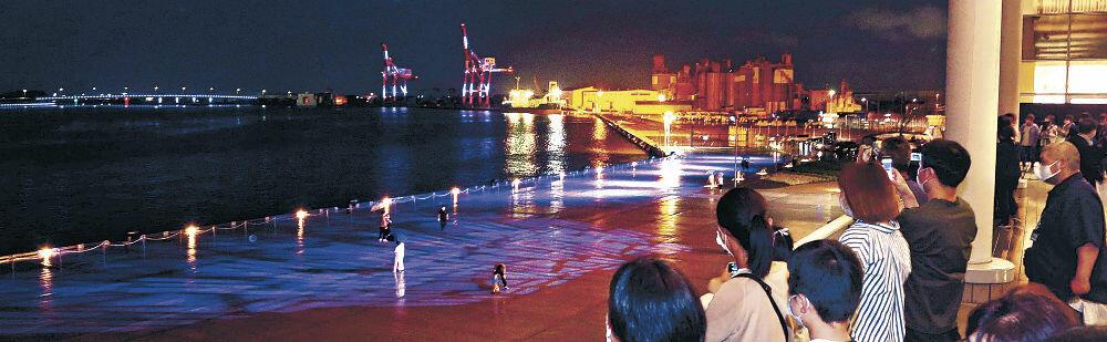 幻想的に照らされた金沢港に見入る来館者=3日午後7時55分、同港クルーズターミナル