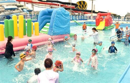 7月4日のプール営業開始を前に、一足早く水遊びを楽しむ園児たち。写真後方は巨大スライダ-=3日、福井県坂井市三国町の「芝政ワールド」