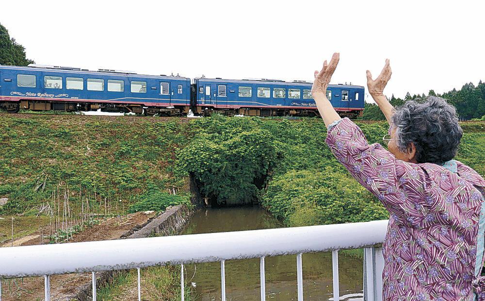 運行を再開した観光列車に手を振る菅原さん=穴水町根木