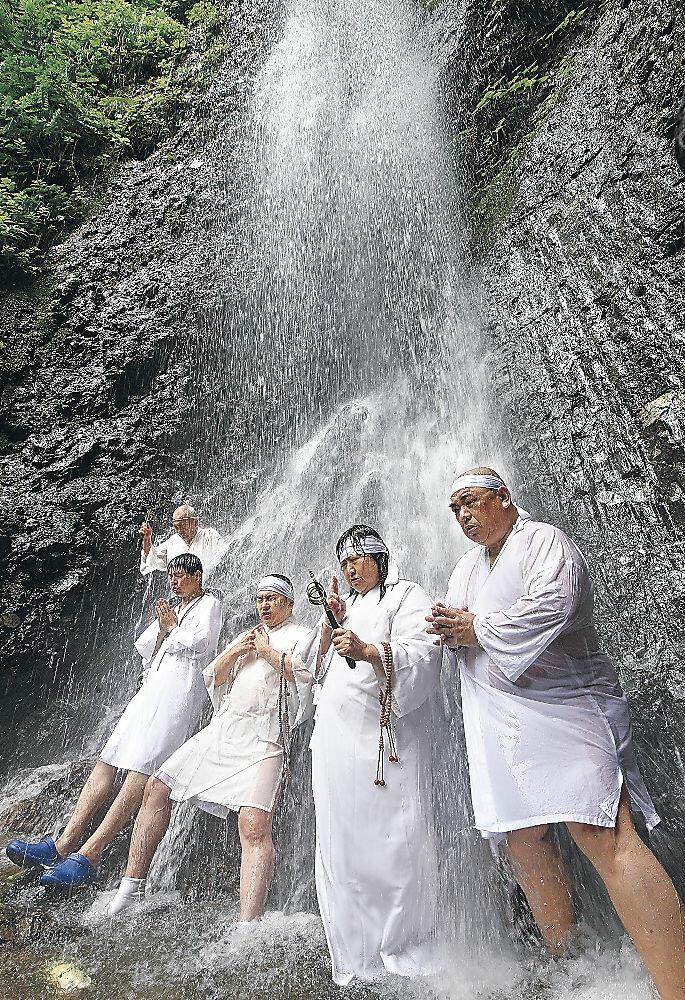 白装束で滝に打たれる人たち=中能登町井田