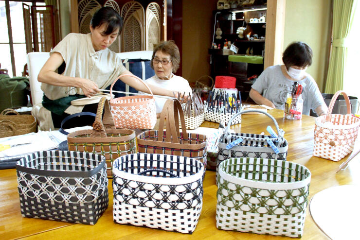 新発田・赤谷産のクラフトバッグ「月岡こまち」を手作りする川辺直子さん(左)ら=新発田市上赤谷