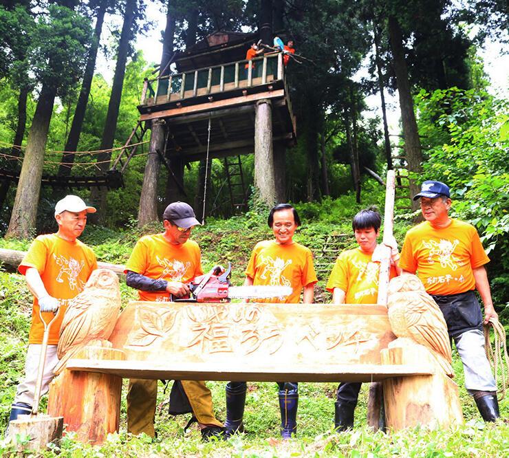 設置した木製ベンチを眺める折谷さん(左から2人目)や石斧の会会員。奥はツリーハウス