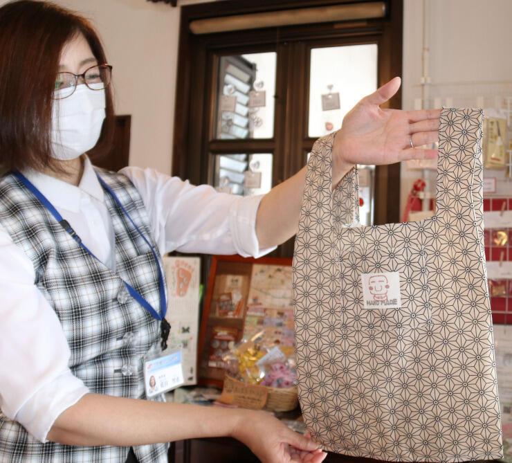万治の石仏のイラストが付いたエコバッグ。下諏訪町の観光案内所には他にも関連グッズが並ぶ