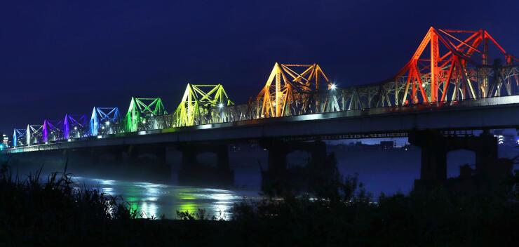 明日への希望を込めた虹色の7色でライトアップされた長生橋=6日、長岡市の信濃川左岸