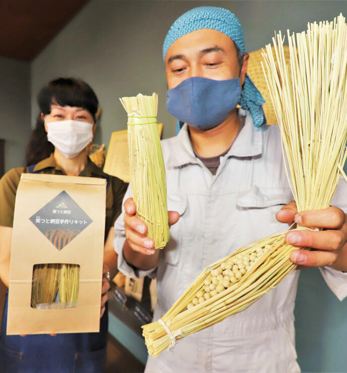 納豆を手作りするためのわらのキットを持つ「未来いいじま」の社員