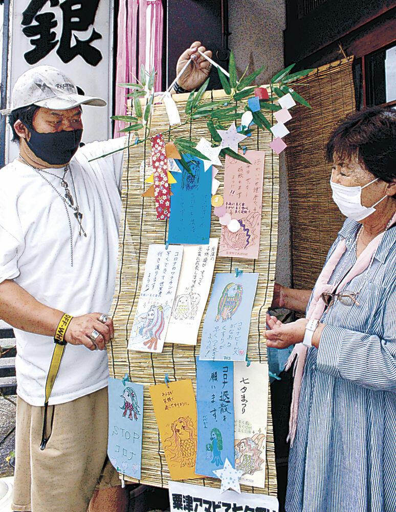 アマビエや願い事が記された短冊を飾り付ける島崎館長(左)=小松市粟津町