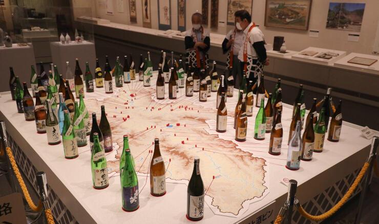 80ある地酒の酒蔵を示した信州の地図。酒瓶を地図の脇にずらりと並べた