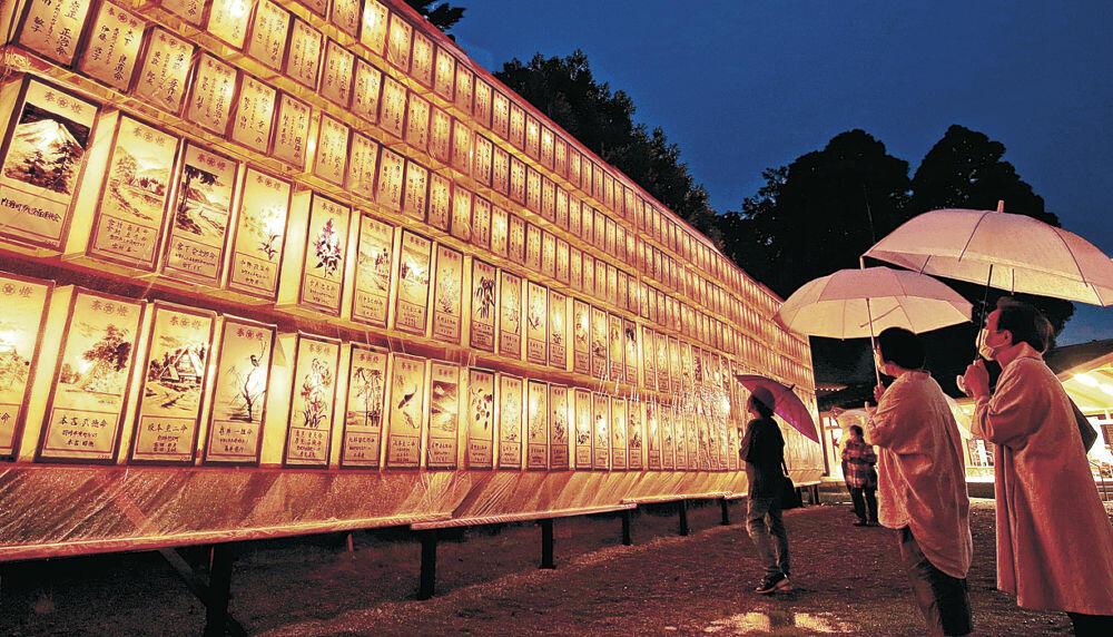献灯あんどんを眺め、戦没者の冥福を祈る参拝者=金沢市の石川護国神社