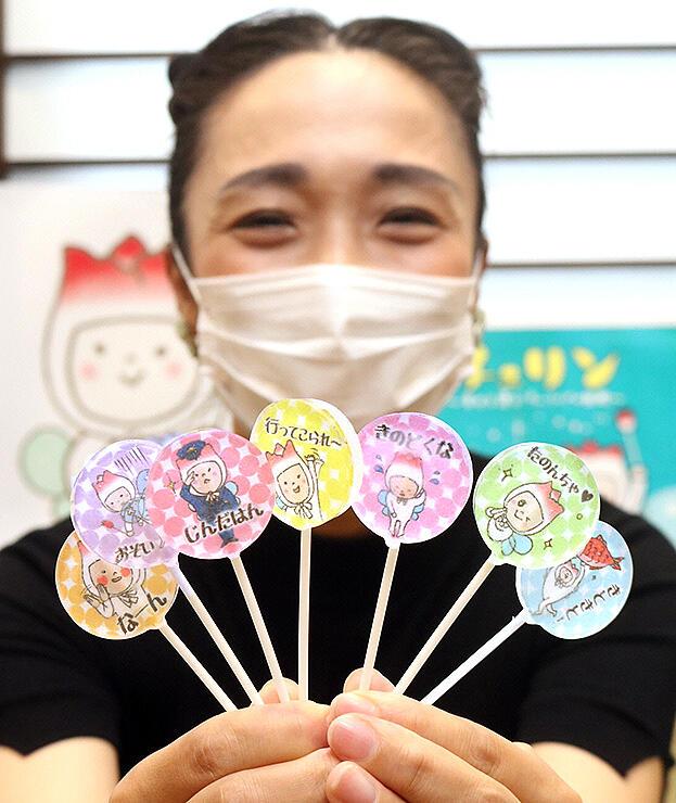 チューリップの妖精「チュリン」のイラストが描かれた7種類の富山弁キャンディーを披露する大井山さん