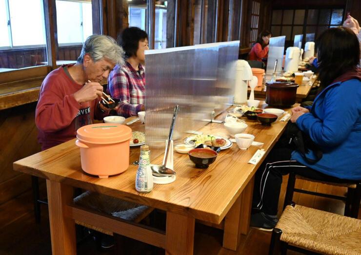感染予防の間仕切りがテーブルに設置された山小屋の食堂=15日