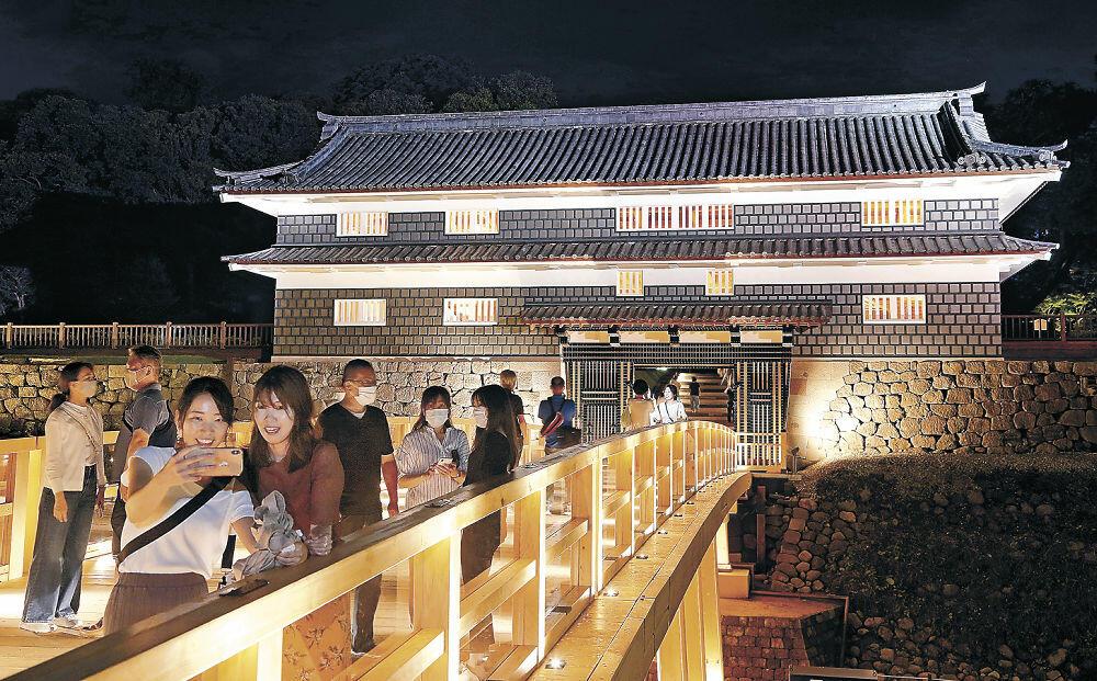 鼠多門と鼠多門橋の一般供用が始まり、ライトアップされた光景を楽しむ来訪者=18日午後8時半、金沢市丸の内