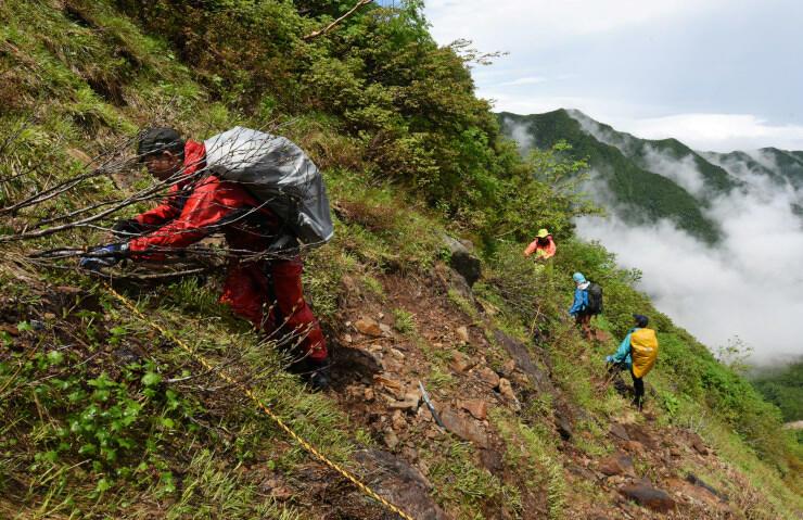 傾斜が急な場所に歩行を補助するロープを張る堀金登山案内人組合のメンバー