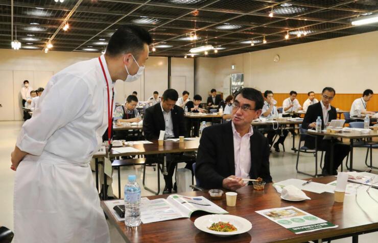 ジビエ料理を試食する河野防衛相(手前右)に説明する藤木さん=20日