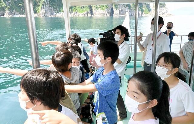 「蘇洞門巡り」で遊覧船での観光を体験する雲浜小6年生たち=7月21日、福井県若狭湾沖