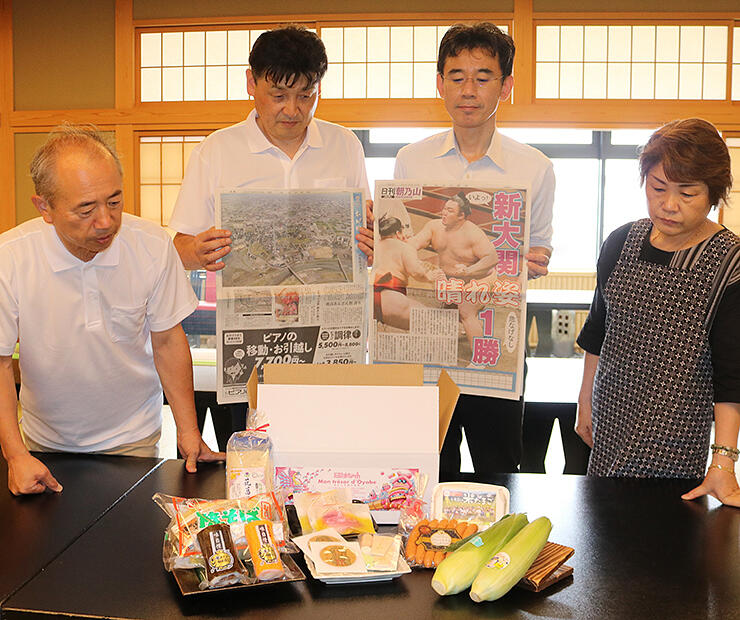 おやべ元気BOXを販売したまっちゃプロジェクトメンバー。「日刊朝乃山」(右)と「空からわが町」(左)を掲載した北日本新聞20日付朝刊も入れた