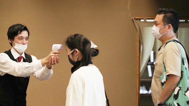 岐阜県から到着し、スタッフ(左)から検温を受ける東さん夫婦=22日午後4時7分、阿智村智里の昼神温泉郷「石苔亭いしだ」