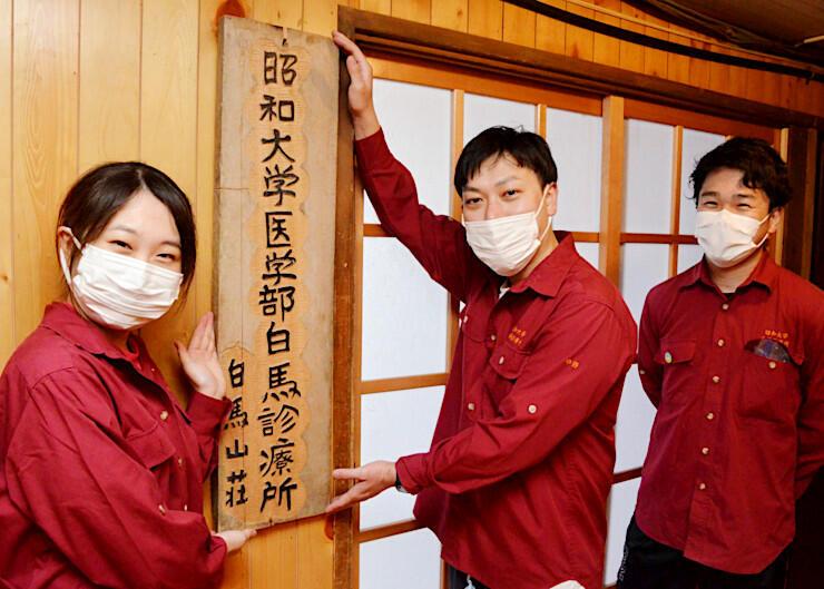 白馬診療所の看板を掲げる昭和大医学部卒業生の研修医=23日、白馬村