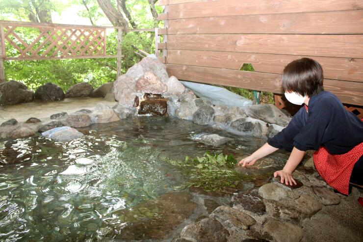 乾燥させた野草を入れた薬草露天風呂=阿賀町広谷乙の「みかぐら温泉ブナの宿 小会瀬」