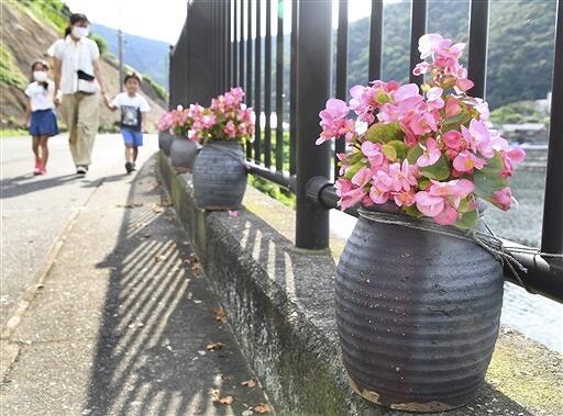 福井県美浜町の日向漁港沿いの県道に並ぶ花が植えられたタコつぼ=7月18日