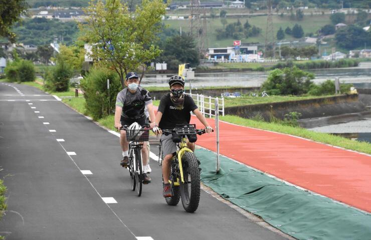 開通したサイクリングロードを自転車で走る人たち