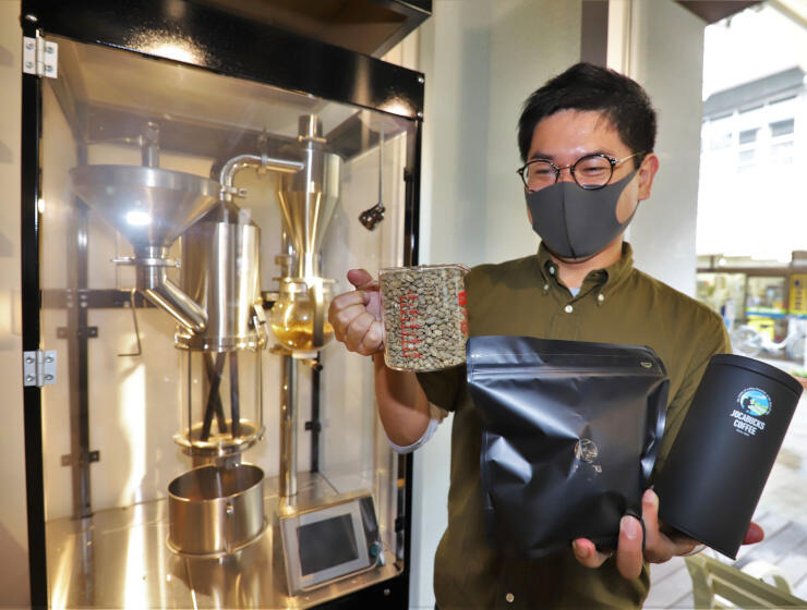 青年海外協力協会(JOCA)本部にある焙煎機の前で販売するコーヒー豆のパックを持つ増田さん