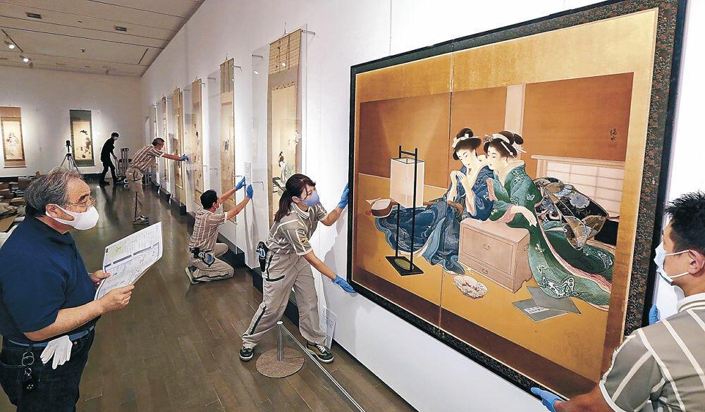 美人画の秀作の展示を進める関係者=金沢21世紀美術館