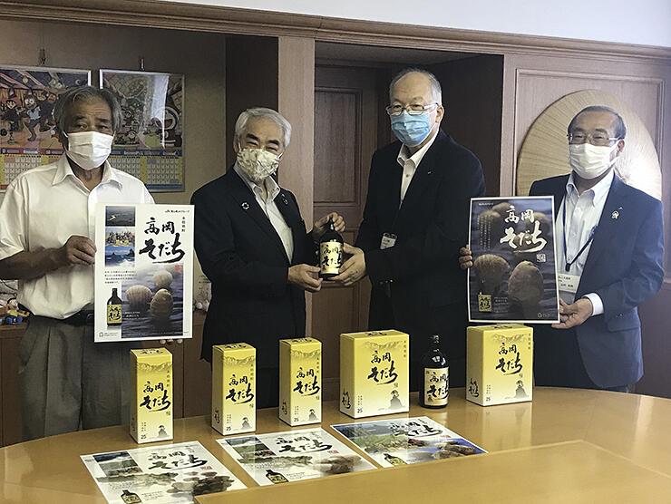 高橋市長(左から2人目)に焼酎を手渡す大井組合長(同3人目)