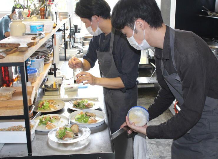 旬の食材をふんだんに使った料理を盛りつける「0256Bistro&Meals」のスタッフ=三条市桜木町