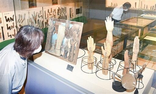 三方石観世音に奉納された手足型が並ぶ企画展=福井県若狭町鳥浜の若狭三方縄文博物館