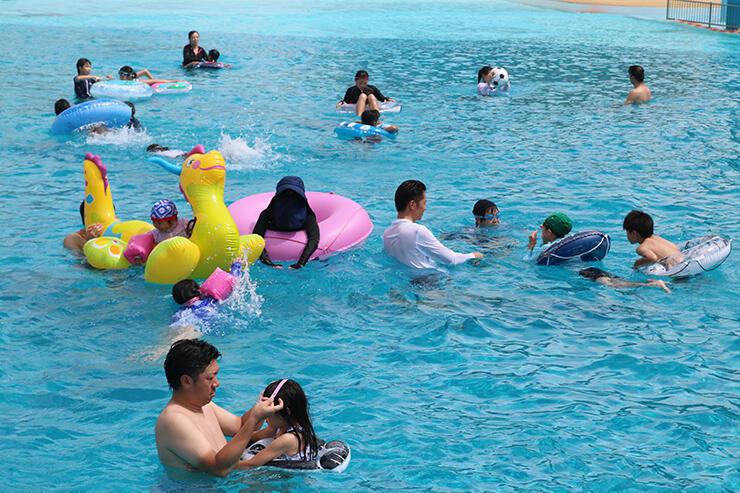 造波プールで波に乗る親子ら=太閤山ランド