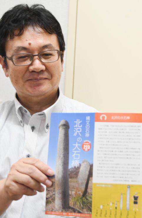 「北沢の大石棒」のパンフレットを手にする桜井さん