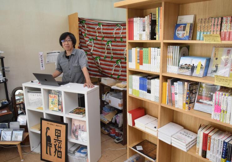 自作の書籍が並ぶ店内で客との交流を楽しみにしている田口さん