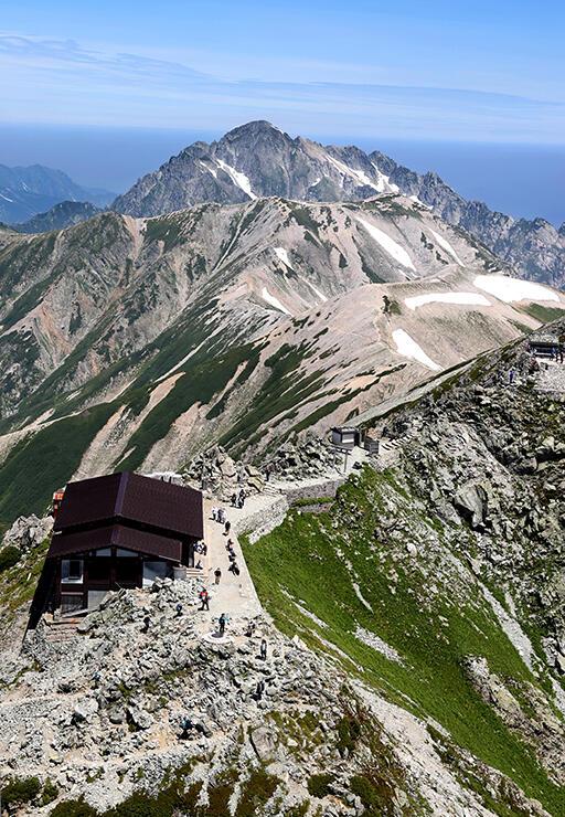 雄大なパノラマを楽しみながら登山する人たち。奥は剱岳=北アルプス・雄山山頂付近
