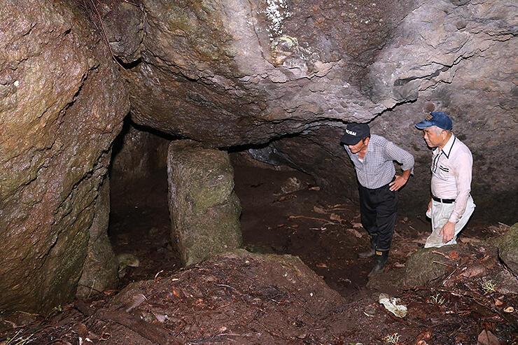 鶴仙和尚が修行したとされる洞窟の内部を調査する平井会長(左)と藤田さん