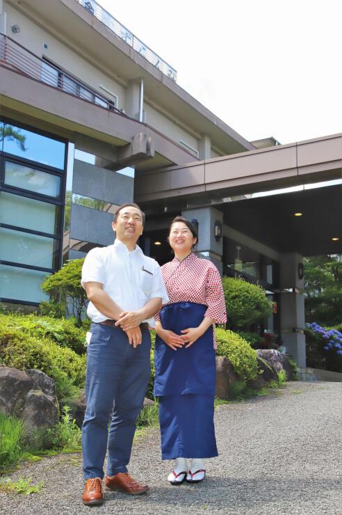 オープンした宿「すずらん颯」の前に立つ松口さん夫妻