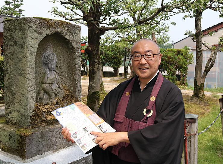 瑞龍寺にある石仏の前でマップを示す四津谷住職