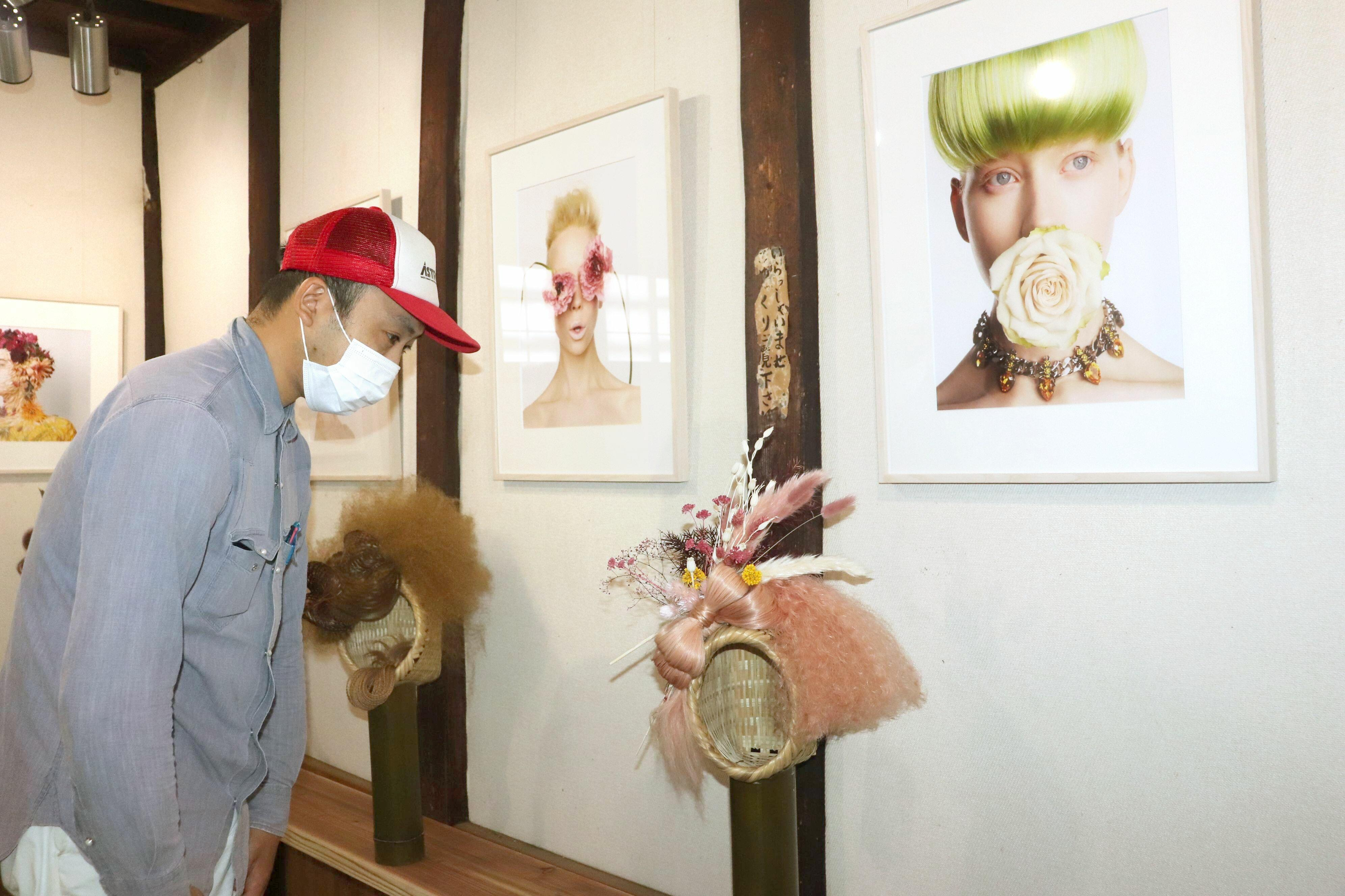 佐渡の竹籠を使った計良宏文さんの個性豊かなヘアメーク作品。写真家・華道家の勅使河原城一さんと生花を使って作成したヘアメークの写真も展示されている=佐渡市金井新保の大慶寺