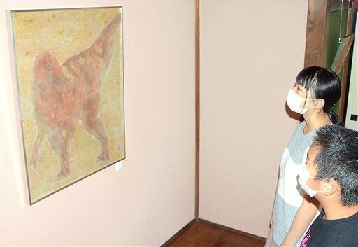 フクイラプトルをモチーフにした日本画に見入る来場者=8月19日、福井県勝山市の花月楼