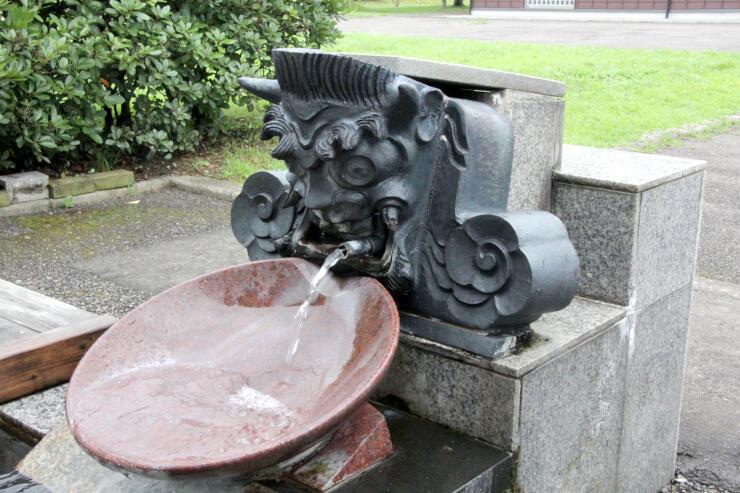 鬼瓦が取り付けられた足湯の湯口。酒呑童子が酒を飲んでいるようだ=燕市国上