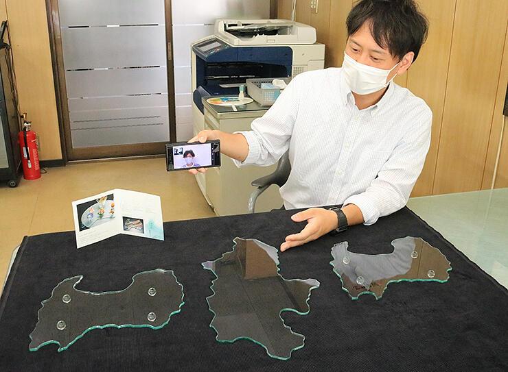 長野県の形をしたガラスの皿(中央)と富山県のガラス皿をリモートで瀧澤さんに紹介する吉森一喜さん