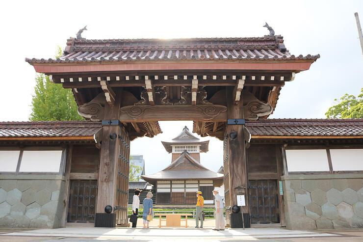 21年ぶりに大戸が開けられた勝興寺の総門。正面奥に鼓堂、左奥には本堂の屋根が門から見える=高岡市伏木古国府