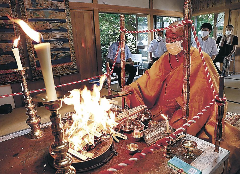 祈りをささげる鹿野住職(手前)と参列者=小松市不動島町の八坂神社不動堂