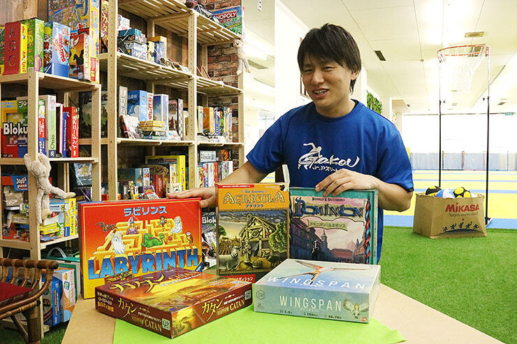 人気のボードゲームを紹介する野原さん。右奥は隣接するスポーツ教室のスペース