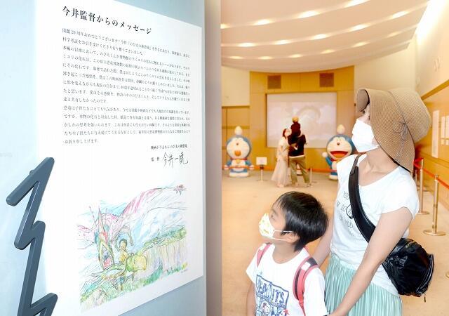 今井監督のメッセージを眺める親子=福井県勝山市の県立恐竜博物館